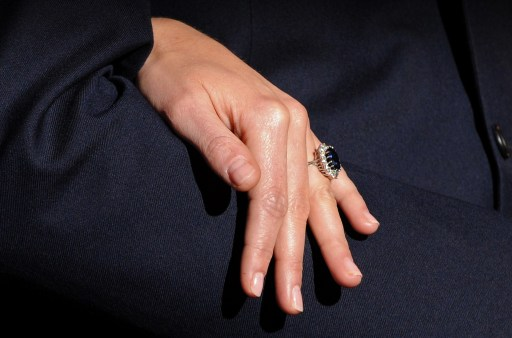 Kate Middleton, fianc?e of Britain's Prince William, shows off her engagement ring as they pose for photographers during a photocall to mark their engagement, in the State Rooms of St James?s Palace, central London on November 16, 2010.  Britain's Prince William has given his fiancee Kate Middleton the engagement ring that belonged to his late mother Diana, Princess of Wales, Clarence House said Tuesday.  The blue sapphire and diamond ring was given to Diana by William's father, Prince Charles, when they became engaged in February 1981. Charles and Diana divorced in 1996 and she was killed in a car crash in Paris the following year.      AFP PHOTO / BEN STANSALL