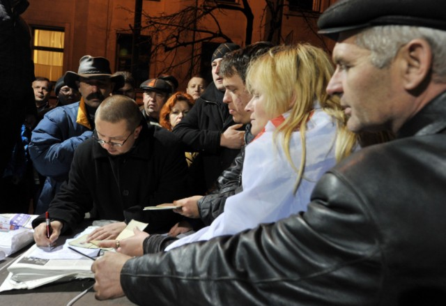 People hold their passports as they put their signatures to hold a national referendum for dissolution of Ukrainian parliament, during a rally in front of President Viktor Yanukovych's office in Kiev, on November 22, 2010. In recent months, small and medium sized business owners have repeatedly criticized the government's plan to unify several laws into a tax code due to enter into force on January 1. AFP PHOTO/ SERGEI SUPINSKY