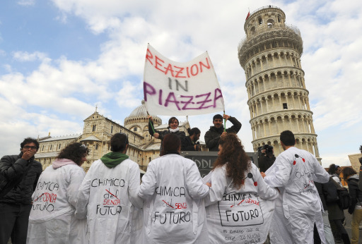"Pisa University students protest near the leaning tower on November 25, 2010 in Pisa against proposed education reforms. Students from several cities protested against the government's proposed reform of the university system and budget cuts that Prime Minister Silvio Berlusconi's government has engaged to carry out by 2013. Students are outraged over cuts of around nine billion euros (12 billion US dollars) and 130,000 jobs in the education system. Banner reads: ""Reaction in the street.""  AFP PHOTO / FABIO MUZZI"