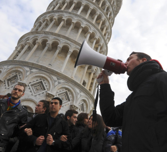 Pisa University students protest near the leaning tower on November 25, 2010 in Pisa against proposed education reforms. Students from several cities protested against the government's proposed reform of the university system and budget cuts that Prime Minister Silvio Berlusconi's government has engaged to carry out by 2013. Students are outraged over cuts of around nine billion euros (12 billion US dollars) and 130,000 jobs in the education system.   AFP PHOTO / FABIO MUZZI