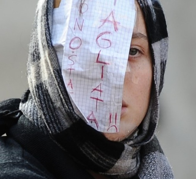 "A student, wearing a mask, reading: ""I was cut,"" protests in front of the Italian Lower House in Rome on November 25, 2010. Students from several cities protest against the government's proposed reform of the university system and budget cuts that Prime Minister Silvio Berlusconi's government has engaged to carry out by 2013. Students are outraged over cuts of around nine billion euros (12 billion US dollars) and 130,000 jobs in the education system.       AFP PHOTO / VINCENZO PINTO"