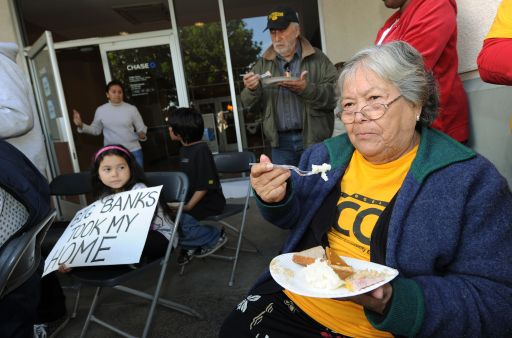 "Julia Botello, 84, eats a meal along with a group of homeowners facing eviction over the holiday period, who protested against their plight outside the bank office by eating their Thanksgiving dinner on it's doorstep, in Long Beach on November 24, 2010.  The Obama administration recently stepped up its efforts to combat a mortgage foreclosure crisis, but said it had so far found no data suggesting knock-on ""systemic"" failures in the financial system. Housing and Urban Development Secretary Shaun Donovan vowed after a high-level White House meeting to make banks found to have erred in processing foreclosures take responsibility, amid fears the episode could stifle the tentative recovery in the housing market and harm the wider economy. Fears of wider exposure escalated in recent weeks after major banks and servicers halted foreclosures to review paperwork, after evidence surfaced that some documents were signed without proper vetting.                                         AFP PHOTO/Mark RALSTON"