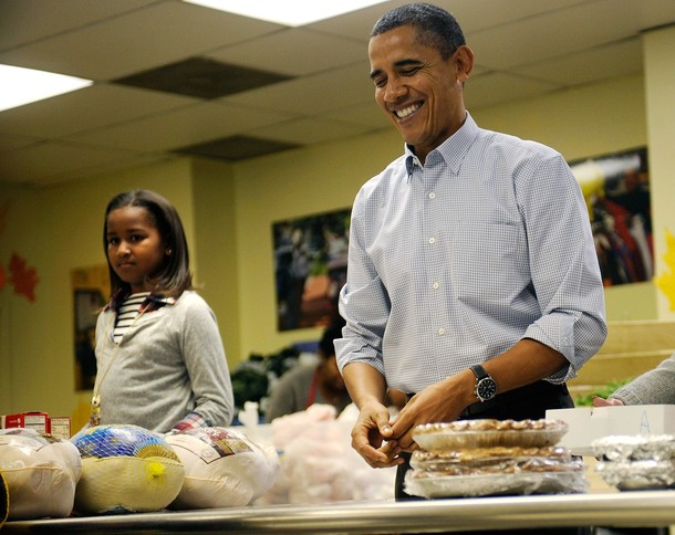 WASHINGTON - NOVEMBER 24:  (AFP OUT)  U.S. President Barack Obama packs and gives bags of food to area residents, with the help of his daughter Sasha, left, ahead of the Thanksgiving Day holiday at Martha's Table on November 24, 2010 in Washington, DC.  The Obama family delivered turkeys and bags of food to needy families at Martha's Table, a 30-year-old non-profit that helps poor children, youth and families with food and clothing.  (Photo by Leslie E. Kossoff-Pool/Getty Images)