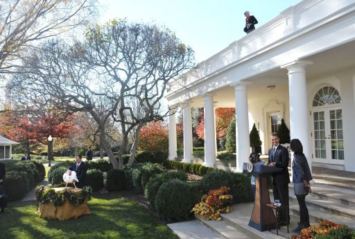 "US President Barack Obama speaks as his daughters Malia (R) and Sasha (3rd R) look on during the annual pardon of the National Thanksgiving Turkey November 24, 2010 in the Rose Garden of the White House in Washington, DC. Supervising ""Apple"" the National Thanksgiving Turkey is National Turkey Federation Chairman Yubert Envia. AFP PHOTO/Mandel NGAN"