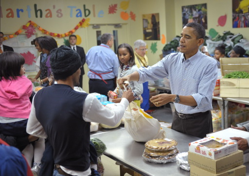 US President Barack Obama and his daughter Sasha (2nd R) distribute food at Martha?s Table a day before Thanksgiving, on November 24, 2010 in Washington, DC. Martha's Table is a non-profit organization that provides food, shelter and clothing to those in need. AFP PHOTO/Mandel NGAN