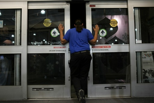 NAPLES, FL - NOVEMBER 26: A Best Buy employee prepares to open the doors to shoppers at dawn during Black Friday, the day after Thanksgiving which commences the holiday gift-buying season on November 26, 2010 in Naples, Florida. Hundreds of shoppers spent the night camped in front of the store to be the first ones in when doors opened at 5am. Black Friday typically features steep discounts on such favorite items as toys and electronics.   Spencer Platt/Getty Images/AFP== FOR NEWSPAPERS, INTERNET, TELCOS & TELEVISION USE ONLY ==