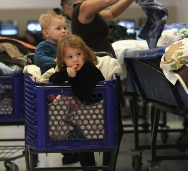 DENVER - NOVEMBER 26: Audrey Holley shops as her children Walter, 18 months, and Aspen, 3, wait in her cart at a Goodwill thrift store on Black Friday, November 26, 2010 in Denver, Colorado. People packed the thrift store on the busiest shopping day of the year, buying toys and clothes in bulk for as cheap as 59 cents a pound.   John Moore/Getty Images/AFP== FOR NEWSPAPERS, INTERNET, TELCOS & TELEVISION USE ONLY ==