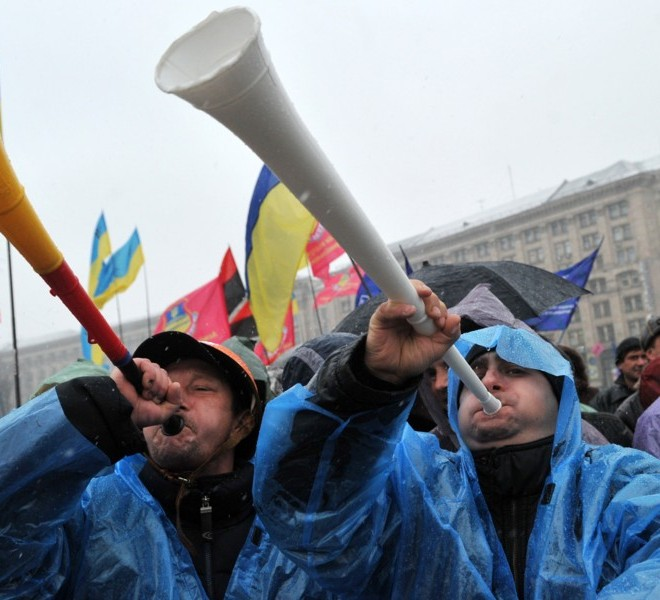 Protesters blow vuvuzelas during a rally on Independence Square in Kiev on November 29, 2010. Thousands of Ukrainians have turned out in noisy demonstrations across the country against the taxes reforms, in a nasty surprise for President Viktor Yanukovych just as he seemed to be asserting his authority after taking power in February. Ukraine has not seen protests on this scale since the 2004 Orange Revolution popular uprising that ousted the old elite and installed Yanukovych's pro-Western predecessors in power. AFP PHOTO/ SERGEI SUPINSKY