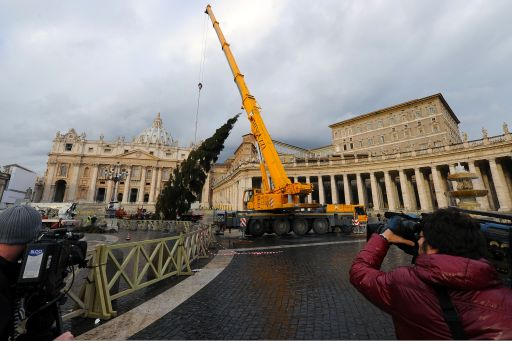 Cameramen film as a crane delivers the Christams tree in St. Peter's square at the Vatican on December 3, 2010. The 94-year-old tree donated from the village of Luson in the italian Alto Adige region is high approximately 34 meters.  AFP PHOTO / ALBERTO PIZZOLI