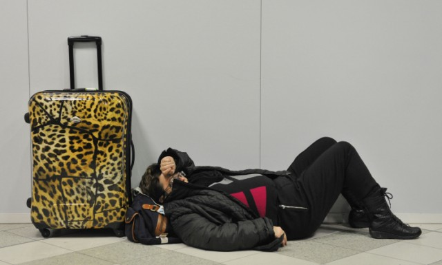 A passenger rests on the floor, after heavy snow closed the runway cancelling flights, at Gatwick Airport in southern England on December 01, 2010.  Britain's transport links with the rest of the world were disrupted by the early winter snowfall as key airports closed Wednesday and international Eurostar train services were cut.  London Gatwick Airport, Europe's eighth busiest passenger air hub, was closed until at least 6:00 am (0600 GMT) Thursday as staff worked on clearing the two runways.      TOPSHOTS/AFP PHOTO / CARL COURT