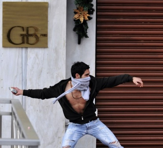 A youth throws a stone at riot police during a demonstration in central Athens on December 6, 2010. Groups of hooded students hurled stones and blocks of wood at windows of banks and shops in the centre of the Greek capital as they marched towards the parliament building to commemorate the death of Alexis Grigoropoulos. AFP PHOTO/ Aris Messinis