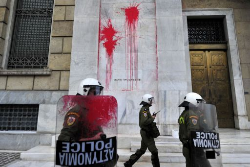 Riot police members, one whose sheild is vovered in paint, walk past splatters on the wall of the Bank of Greece's headquarters during a demonstration in central Athens on December 6, 2010.  Groups of hooded students hurled stones and blocks of wood at windows of banks and shops in the centre of the Greek capital as they marched towards the parliament building to mark the 2nd year anniversary of the death of teenager Alexis Grigoropoulos who was shot dead by police.  AFP PHOTO/ Aris Messinis