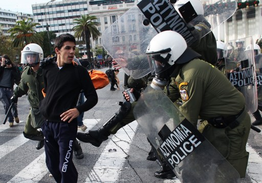 Riot police attack a youth during a demonstration in central Athens on December 6, 2010. Groups of hooded students hurled stones and blocks of wood at windows of banks and shops in the centre of the Greek capital as they marched towards the parliament building to mark the 2nd year anniversary of the death of teenager Alexis Grigoropoulos who was shot dead by police.  AFP PHOTO/ Angelos Tzortzinis
