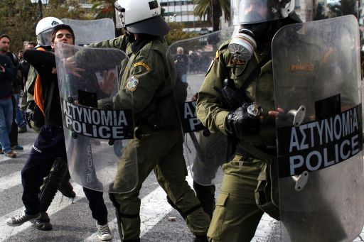 Riot police attack a youth during a rally in Athens on December 6, 2010. Groups of hooded students hurled stones and blocks of wood at windows of banks and shops in the centre of the Greek capital as they marched towards the parliament building to mark the 2nd year anniversary of the death of teenager Alexis Grigoropoulos who was shot dead by police.  AFP PHOTO/ Angelos Tzortzinis