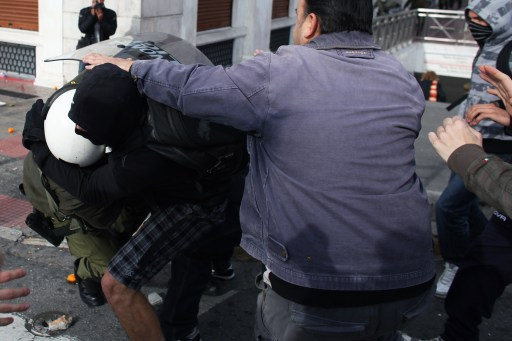A youth attacks a riot police member during a demonstration in central Athens on December 6, 2010. Groups of hooded students hurled stones and blocks of wood at windows of banks and shops in the centre of the Greek capital as they marched towards the parliament building to mark the 2nd year anniversary of the death of teenager Alexis Grigoropoulos who was shot dead by police.  AFP PHOTO/ Angelos Tzortzinis