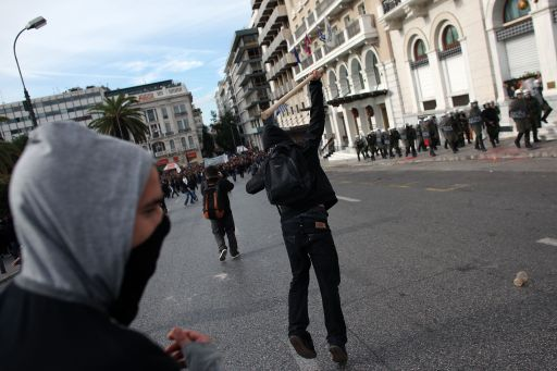 A youth throws an object at riot police during a demonstration in central Athens on December 6, 2010. Groups of hooded students hurled stones and blocks of wood at windows of banks and shops in the centre of the Greek capital as they marched towards the parliament building to mark the 2nd year anniversary of the death of teenager Alexis Grigoropoulos who was shot dead by police.  AFP PHOTO/ Angelos Tzortzinis