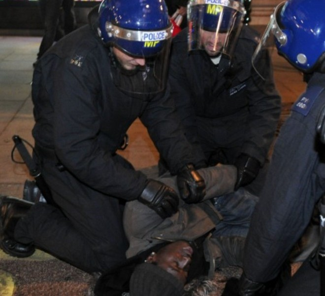 Police officers help a man who was knocked over as they clashed on Oxford Street, central London, during protests against an increase in fees on December 9, 2010. Rioters battled police outside parliament and attacked a car carrying the heir to the throne Prince Charles on Thursday as Britain's coalition survived a major test in a vote to raise university fees. AFP PHOTO / CARL COURT