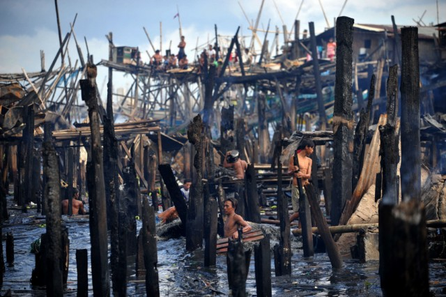 AFP PICTURE OF THE YEAR 2010 Children salvage belongings and materials from the aftermath of a fire which gutted a sprawling shanty town at the bay of Navotas, Manila on August 27, 2010. Some 200 homes were damaged, leaving around 300 families homeless, local radio reported.  AFP PHOTO/NOEL CELIS