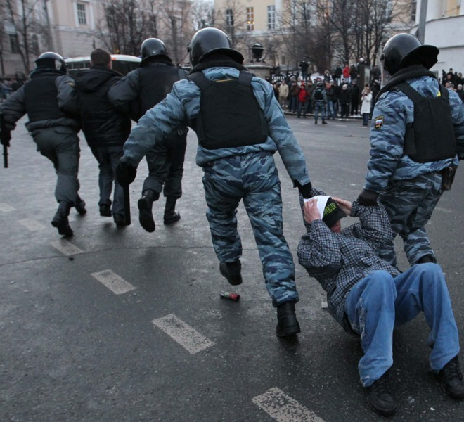 A Football fan is arrested by two policemen following clashes with riot police in central Moscow on December 11, 2010,  after Yegor Sviridov, 28, a dedicated fan of the Spartak Moscow football team  was shot dead on December 4, 2010. Witnesses said Sviridov was shot in the head  in a mass fight with men from the Russian Caucasus. Another Spartak fan was shot in the stomach, the Kommersant daily reported. The incident exposed the close relationship between football fans and nationalist groups.AFP PHOTO/ ALEXEY SAZONOV