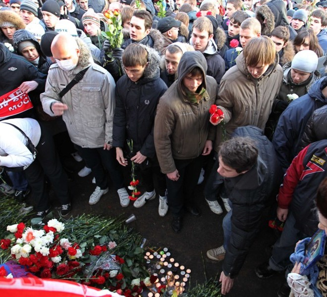 People put flowers on December 11, 2010 in Moscow, at the place where Yegor Sviridov, a supporter of Spartak Moscow football team was killed during a street fight with natives of Caucasus a few days ago. Some 6.000 football fans from different clubs gathered to commemorate their mate.      AFP PHOTO / ALEXEY SAZONOV