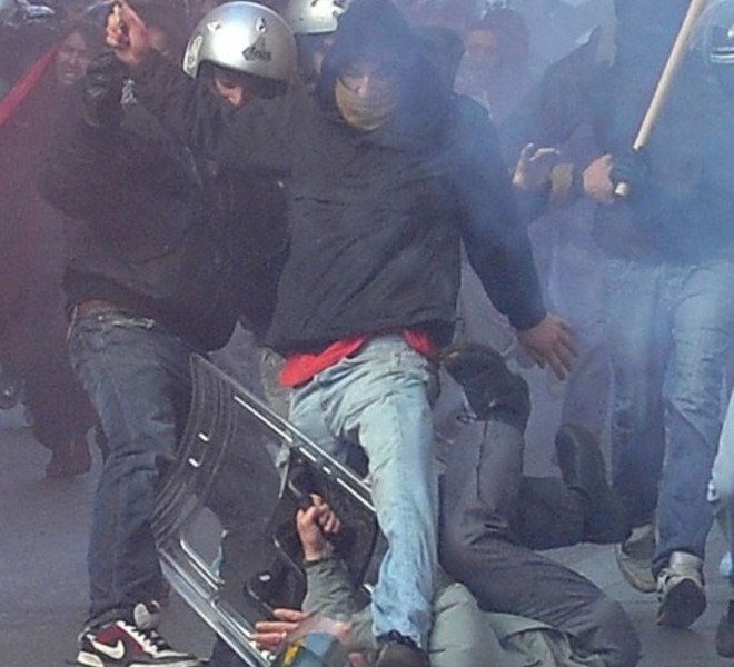 policeman (C-on ground) is being surrounded and hit by demonstrators during a protest of youths to demand a change of government as parliament met to hold a crucial vote that could topple Prime Minister Silvio Berlusconi on December 14, 2010 in Via del Corso in Rome. Italian Prime Minister Silvio Berlusconi scraped through a crucial confidence vote in the lower house of parliament by 314 votes in favour and 311 against. AFP PHOTO / ALBERTO PIZZOLI