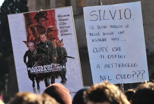 "Demonstrators hold a placard reading ""Silvio, if  beautiful girls are better than being gay, why do you still fuck us in the ass ?"" during a protest of youths to demand a change of government as parliament met to hold a crucial vote that could topple Prime Minister Silvio Berlusconi on December 14, 2010 in Via del Corso in Rome. Italian Prime Minister Silvio Berlusconi scraped through a crucial confidence vote in the lower house of parliament by 314 votes in favour and 311 against. AFP PHOTO / ALBERTO PIZZOLI"