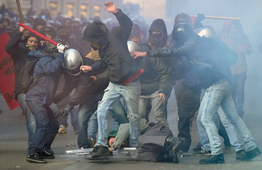 A policeman (C-on ground) is being surrounded and hit by demonstrators during a protest of youths to demand a change of government as parliament met to hold a crucial vote that could topple Prime Minister Silvio Berlusconi on December 14, 2010 in Via del Corso in Rome. Italian Prime Minister Silvio Berlusconi scraped through a crucial confidence vote in the lower house of parliament by 314 votes in favour and 311 against. TOPSHOTS / AFP PHOTO / ALBERTO PIZZOLI