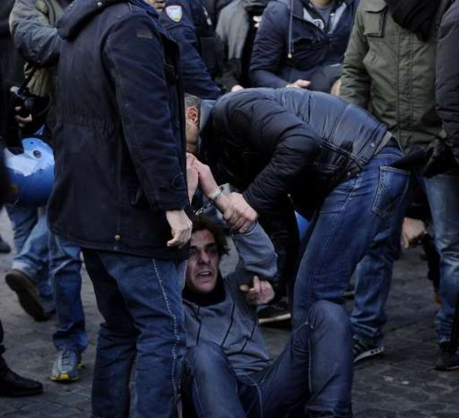 A protester is being arrested during a protest to demand a change of government as parliament met to hold a crucial vote that could topple Prime Minister Silvio Berlusconi on December 14, 2010 in Rome. Italian Prime Minister Silvio Berlusconi scraped through a crucial confidence vote in the lower house of parliament by 314 votes in favour and 311 against.  AFP PHOTO / FILIPPO MONTEFORTE