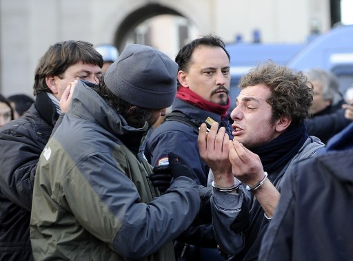 A protester (R) is being arrested during a protest to demand a change of government as parliament met to hold a crucial vote that could topple Prime Minister Silvio Berlusconi on December 14, 2010 in Rome. Italian Prime Minister Silvio Berlusconi scraped through a crucial confidence vote in the lower house of parliament by 314 votes in favour and 311 against.  AFP PHOTO / FILIPPO MONTEFORTE