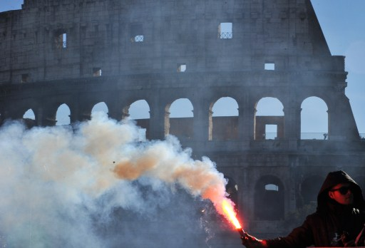 Youth burns a flares near the Colosseo during a protest to demand a change of government as parliament met to hold a crucial vote that could topple Prime Minister Silvio Berlusconi on December 14, 2010 in Rome. Italian Prime Minister Silvio Berlusconi scraped through a crucial confidence vote in the lower house of parliament by 314 votes in favour and 311 against.   AFP PHOTO / ALBERTO PIZZOLI