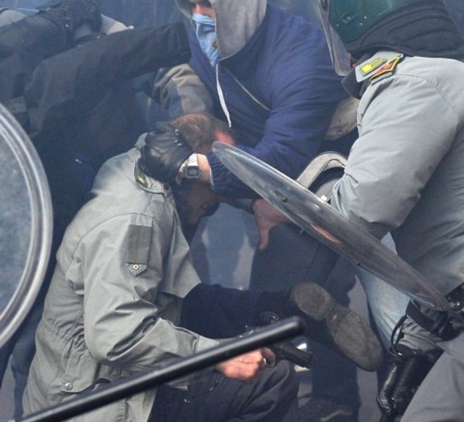 A policeman (C-on ground) holds his gun as he is surrounded and hit by demonstrators during a protest of youths to demand a change of government as parliament met to hold a crucial vote that could topple Prime Minister Silvio Berlusconi on December 14, 2010 in Via del Corso in Rome. Italian Prime Minister Silvio Berlusconi scraped through a crucial confidence vote in the lower house of parliament by 314 votes in favour and 311 against. AFP PHOTO / ALBERTO PIZZOLI