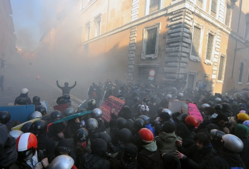 Youths face policemen during a protest to demand a change of government as parliament met to hold a crucial vote that could topple Prime Minister Silvio Berlusconi on December 14, 2010 in Rome. Protest organisers estimated the number in Rome alone at 100,000.  AFP PHOTO / ALBERTO PIZZOLI