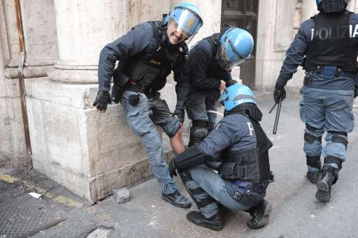 An injured policeman is treated by colleagues during a protest to demand a change of government as parliament met to hold crucial vote that could topple Prime Minister Silvio Berlusconi on December 14, 2010 in Rome. Italian Prime Minister Silvio Berlusconi scraped through a crucial confidence vote in the lower house of parliament by 314 votes in favour and 311 against.  AFP PHOTO / VINCENZO PINTO