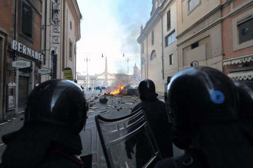 Police march to Piazza del Popolo after vehicules were set on fire during a protest to demand a change of government as parliament met to hold a crucial vote that could topple Prime Minister Silvio Berlusconi on December 14, 2010 in Rome. Italian Prime Minister Silvio Berlusconi scraped through a crucial confidence vote in the lower house of parliament by 314 votes in favour and 311 against.  AFP PHOTO / VINCENZO PINTO