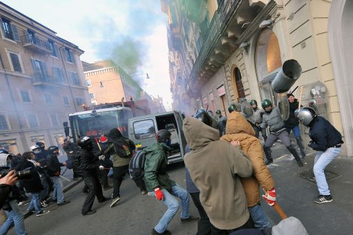 Youths face policemen during a protest to demand a change of government as parliament met to hold a crucial vote that could topple Prime Minister Silvio Berlusconi on December 14, 2010 in Via del Corso in Rome. Italian Prime Minister Silvio Berlusconi scraped through a crucial confidence vote in the lower house of parliament by 314 votes in favour and 311 against. AFP PHOTO / ALBERTO PIZZOLI