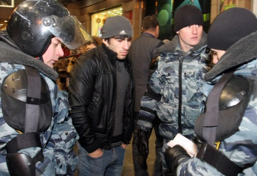 Russian riot policemen examine an ID of a man at the Kievsky train station in Moscow on December 15, 2010. Moscow police arrested more than 700 people Wednesday across the city centre in a bid to prevent ethnic clashes from erupting following the deadly shooting of a football fan, a spokesman said. AFP PHOTO / ANDREY SMIRNOV