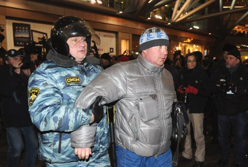 Russian riot police officers detain a protestor in central Moscow on December 15, 2010 during a demonstration for Yegor Sviridov, 28, a dedicated fan of the Spartak Moscow football team shot dead on December 4, 2010. Moscow police arrested more than 700 people Wednesday across the city centre in a bid to prevent ethnic clashes from erupting following the deadly shooting of a football fan, a spokesman said.   AFP PHOTO/ ALEXANDER NEMENOV