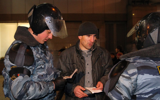 Russian riot policemen examine an ID of a man at the Kievsky train station in Moscow on December 15, 2010. Moscow police arrested more than 700 people Wednesday across the city centre in a bid to prevent ethnic clashes from erupting following the deadly shooting of a football fan, a spokesman said. AFP PHOTO / ALEXEY SAZONOV
