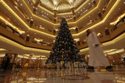 An Emirati man walks past an 11-million-dollar Christmas tree at the Emirates Palace hotel in the Emirati capital Abu Dhabi on December 15, 2010. Christmas came in extravagant fashion to the Muslim desert emirate of Abu Dhabi as a glitzy hotel unveiled a bejewelled Christmas tree valued at more than 11 million dollars. AFP PHOTO/STR