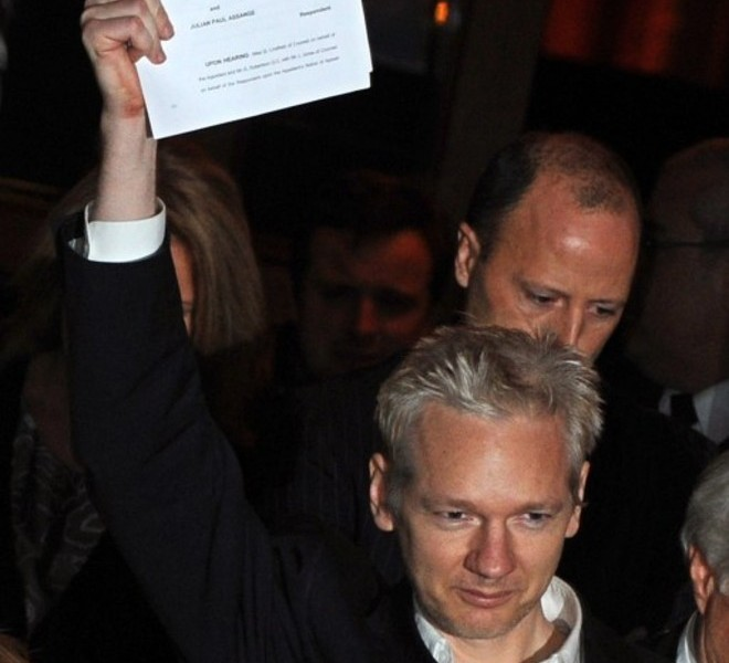 WikiLeaks founder Julian Assange holds up his legal papers as he celebrates outside the High Court in central London, on December 16, 2010. The founder of the WikiLeaks website Julian Assange was granted bail on Thursday by the High Court in London, which rejected an appeal against him being released even under stringent conditions. TOPSHOTS/AFP PHOTO/BEN STANSALL