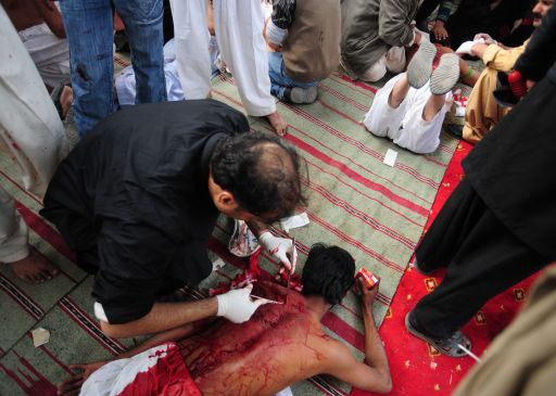 Pakistani Shiite scouts treat injured Shiite Muslims after they beat themselves as part of the Ashura observance in Islamabad on December 16, 2010. Ashura, is the final day of 10 days of mourning for the killing of the grandson of Prophet Mohammad in the year 680AD. Sunnis mark it quietly but Shiites hold public displays of grief, including flaying their backs with whips and chains which sometimes have small blades attached to their ends.  AFP PHOTO / Farooq NAEEM