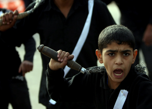 An Iraqi Shiite boy flagellate himself outside a mosque during a ritual in the capital Baghdad on December 16, 2010, during the Ashura commemorations marking the 7th century killing of Imam Hussein, the grandson of Prophet Mohammed, in the Battle of Karbala in central Iraq. AFP PHOTO/AHMAD AL-RUBAYE