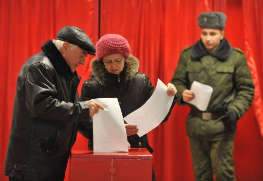 People cast their votes during presidential elections in one of military units near Minsk on December 19, 2010. Belarus went to the polls in presidential elections expected to hand a fourth term to its unpredictable strongman Alexander Lukashenko, extending his grip on power for another five years. Lukashenko, who has been at the helm of this poor ex-Soviet state for the past 16 years, is running against an array of nine opposition candidates. AFP PHOTO/ VIKTOR DRACHEV