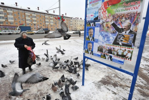 A woman feeds pigeons near a pre-election poster in Minsk on December 17, 2010.  Presidential candidates in Belarus made a final push for votes Friday two days ahead of elections, with few doubting the dominance of incumbent strongman Alexander Lukashenko after a low-key campaign. / AFP PHOTO / VIKTOR DRACHEV