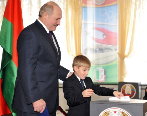 Nikolay Lukashenko casts as his father Belkarus President Alexander Lukashenko stands near during voting in Minsk on December 19, 2010. Belarus went to the polls Sunday in presidential elections expected to hand a fourth term to its unpredictable strongman Alexander Lukashenko, extending his grip on power for another five years. Lukashenko, who has been at the helm of this poor ex-Soviet state for the past 16 years, is running against an array of nine opposition candidates. AFP PHOTO/ VIKTOR DRACHEV