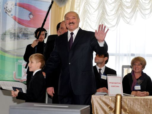 Belarus President Alexander Lukashenko waves to journalists as he arrives to vote in Minsk on December 19, 2010. Belarus went to the polls  in presidential elections expected to hand a fourth term to its unpredictable strongman Alexander Lukashenko, extending his grip on power for another five years. Lukashenko, who has been at the helm of this poor ex-Soviet state for the past 16 years, is running against an array of nine opposition candidates. AFP PHOTO/ VIKTOR DRACHEV