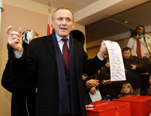 "Belarus presidential candidate Vladimir Neklyayev displays his ballot signed ""New election without Lukashenko"" in a polling station in Minsk, on December 19, 2010. Belarus went to the polls today in presidential elections expected to hand a fourth term to its unpredictable strongman Alexander Lukashenko, extending his grip on power for another five years. Lukashenko, who has been at the helm of this poor ex-Soviet state for the past 16 years, is running against an array of nine opposition candidates. AFP PHOTO/  MAKSIM MALINOUSKI"