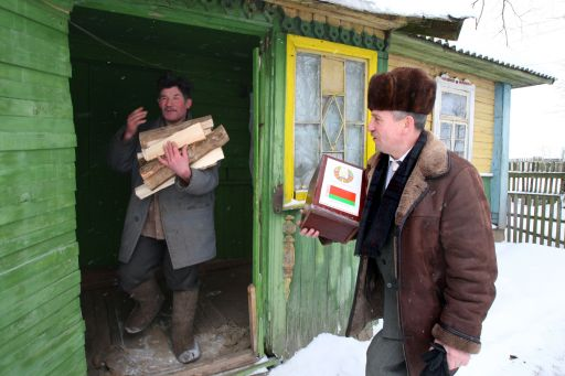 A member of election commission passes a man holding firewood during voting in Vasilkovo village, some 45 km from Minsk.on December 19, 2010. Belarus went to the polls Sunday in presidential elections expected to hand a fourth term to its unpredictable strongman Alexander Lukashenko, extending his grip on power for another five years. Lukashenko, who has been at the helm of this poor ex-Soviet state for the past 16 years, is running against an array of nine opposition candidates. AFP PHOTO/ ALEXEY GROMOV