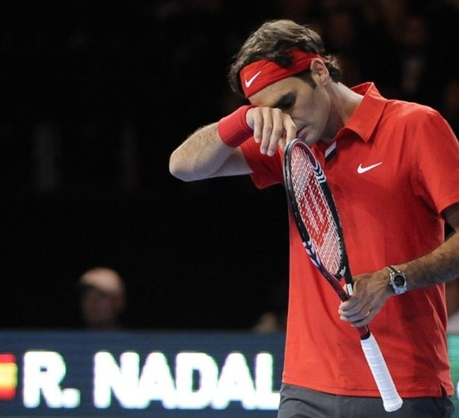"Switzerland's Roger Federer wipes his face during a charity tennis game against Spain's Rafael Nadal on December 21, 2010 in Zurich. ""The Match for Africa"" is organized to raise money for the Roger Federer Foundation which supports sporting activities for underprivileged children in Africa and in Switzerland. AFP PHOTO / FABRICE COFFRINI"