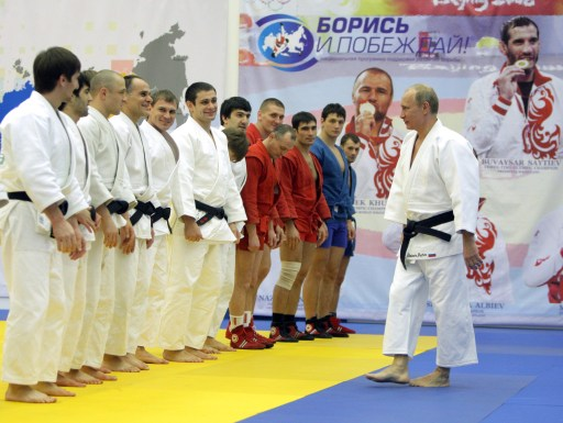 "Russia's Prime Minister Vladimir Putin (R) speaks with a group of judokas at the ""Moscow"" sports complex in St Petersburg, on December 22, 2010 where he took part in a judo training session.   AFP PHOTO/ RIA-NOVOSTI POOL/ ALEXEY DRUZHININ"